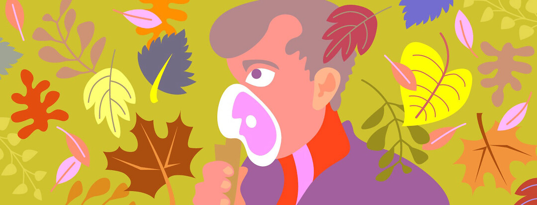 a man uses a nebulizer as colorful autumn leaves swirl around him